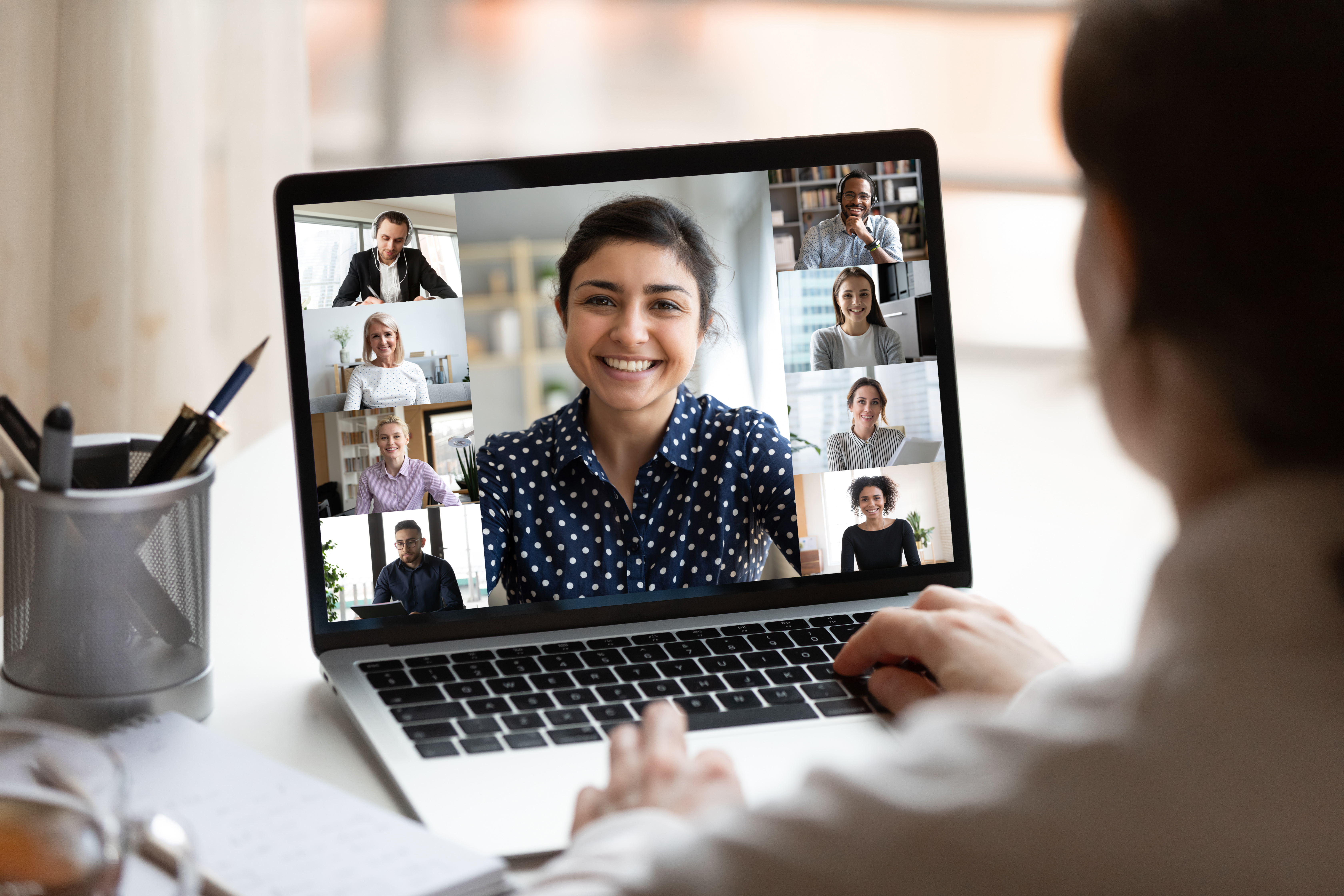 Person viewing an online group meeting/webinar with other individuals on screen.